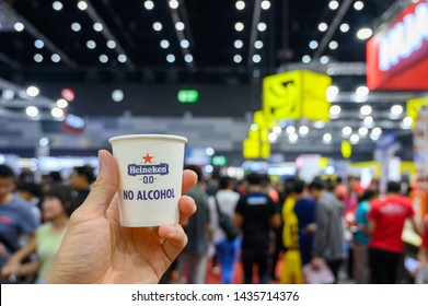 Bangkok, THAILAND - Jun 01, 2019.  Heineken 0.0 paper glass in the hand with blurred background. Heineken 0.0 is a non-alcoholic beer made from natural ingredients. - selective focus image.