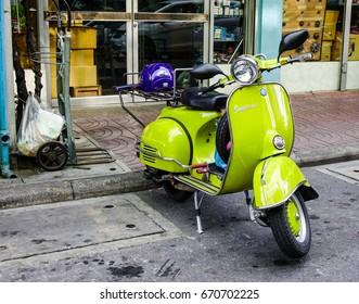 Bangkok, Thailand - Jun 16, 2017. Green Vespa scooter parked at old town in Bangkok, Thailand.