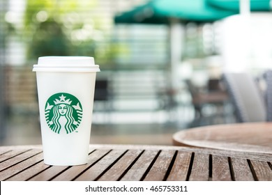 Bangkok, Thailand - Jun 29, 2016 : Starbucks take away coffee cup on wood table in Starbucks coffee shop