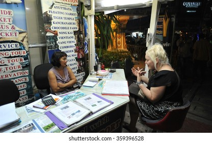 BANGKOK, THAILAND - JUN 30, 2013: Nighttime view of a tourist consulting a travel agent on Khao San Road. The road is famous as backpackers' haven with budget accommodation starting from $6 or B200.