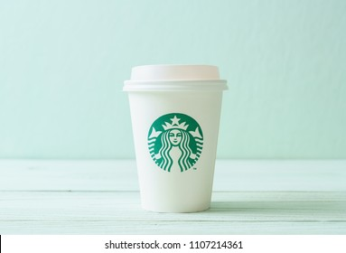 BANGKOK, THAILAND - JUN 5, 2018: White coffee cup with Starbucks logo on wood background. Starbucks is the world's largest coffee house with over 20,000 stores in 61 countries.
