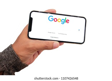 BANGKOK, THAILAND - JUN 6, 2018 :  close up on man hand hold iphone X for searching on www.google.com, iPhone X was created and developed by the Apple inc.