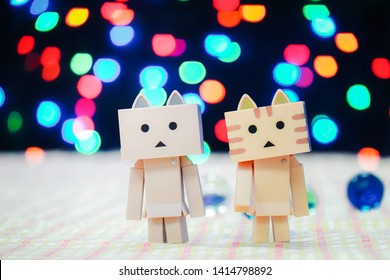 BANGKOK, THAILAND - June 01,2019 : Love  Concept : A Couple  paper cat box dolls standing  with colorful night light bokeh.