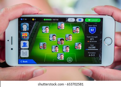 Bangkok, Thailand - June 03, 2017: Hand hold and playing PES 2017 (Pro Evolution Soccer) on an iPhone 6s running iOS. PES is a popular online game in iPad/iPhone/iPod/Android game created by KONAMI.