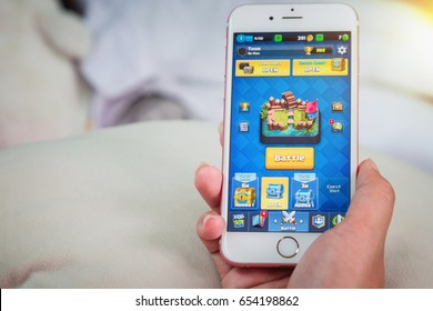 Bangkok, Thailand - June 03, 2017: Hand hold and playing battle Clash Royale on an iPhone 6s running iOS. Clash Royale is a popular online game in iPad/iPhone/iPod/Android game created by Supercell.