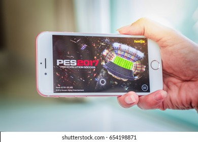 Bangkok, Thailand - June 03, 2017: Hand hold, start loading PES 2017 (Pro Evolution Soccer) on an iPhone 6s running iOS. PES 2017 is a popular online game in iPad/iPhone/Android game created by KONAMI