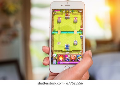 Bangkok, Thailand - June 03, 2017: Hand hold and playing Clash Royale on an iPhone 6s running iOS. Clash Royale is a popular online game in iPad/iPhone/iPod/Android game created by Supercell.