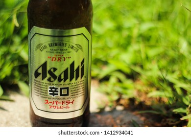 Bangkok Thailand- June 1, 2019: A bottle of Asahi Beer On the lawn . Asahi was founded in Osaka, Japan in 1889 as the Osaka Beer Company.