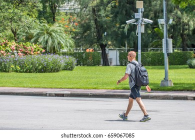 Bangkok, Thailand - June 10, 2017: Walking backpacker with wearing sunglasses and wireless sports in-ear headphone in Lumpini park with security camera and tree background