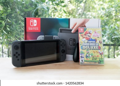 Bangkok, Thailand - June 10, 2019 : Nintendo Switch, video game console for home or portable gaming with box of Mario deluxe switch game