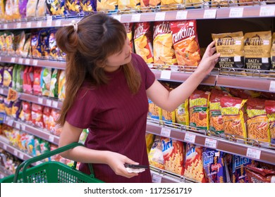 Bangkok, THAILAND - JUNE 11 2018: A young woman chooses snack at The Bright Supermarket. Asian girl purchases snack at a departmen store.