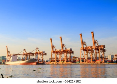 BANGKOK, THAILAND - JUNE 13, 2017:Logistics and transportation of Container Cargo ship and Container Vessel with working crane bridge in shipyard at sunrise for logistic import and export.