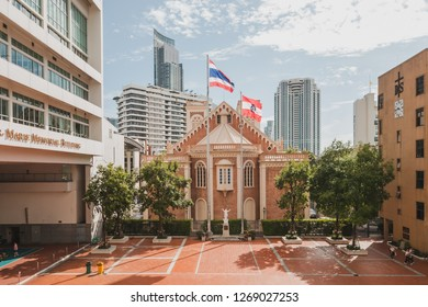 Bangkok, Thailand - June 14, 2017: Assumption Cathedral photographed from Assumption College with Thai flag and Assumption College flag with skyscraper in the background