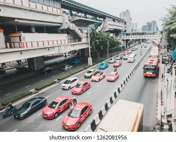 Bangkok, Thailand - June 15, 2017: Colorful taxi and buses passing by Jatujak park with a bus and taxi stop in front under Mo Chit BTS (Metro) Station.