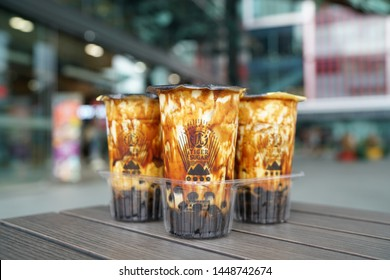 BANGKOK, THAILAND - JUNE 15, 2019: Bubble Milk Tea - Group of  plastic glass of fresh milk with black sugar syrup (Kuromitsu) and hot black pearl (Boba) topped with cream cheese foam on blurred backgr