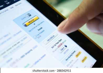 Bangkok, Thailand - June 17, 2015  : Unidentified human finger touch on screen of tablet device on 'Add to Wish List' button in Amazon ,largest famous online shopping website, to buy some product