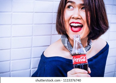 BANGKOK, THAILAND - June 18, 2018:  Woman holding a bottle of coke Have a happy smile. Coca Cola is American beverage company was founded in 1886 by pharmacist.