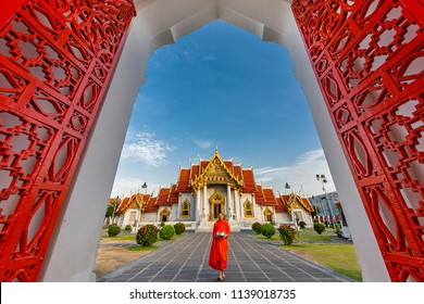 BANGKOK, THAILAND - JUNE 18, 2018: Monk holds his bowl to collect food and offerings at the gate of the Marble Temple known also as Wat Benchamabopit Dusitvanaram in Bangkok, Thailand.