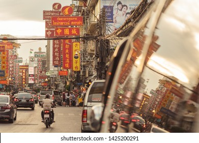 Bangkok, Thailand - June 2, 2019: the main artery of Chinatown, Yaowarat Road in the evening, with its large signboards written in Chinese and reflection in the window of a parked car.