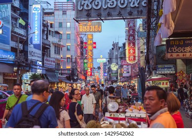 Bangkok, Thailand - June 2, 2019: a diverse crowd walks along Yaowarat Road with its Chinese and Thai signboards in the evening. Yaowarat is the main artery of Chinatown, a popular tourist attraction.