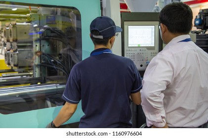 Bangkok, Thailand - June 20, 2018: worker operate industrial plastic injection molding press machine in Manufacturing Expo 2018