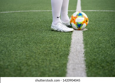 Bangkok / Thailand - June 2019 : A football player is training on turf ground with Asics DS light 3 football boot model which is design for light weight and speedy player. Selected focus photo.