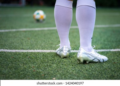 Bangkok / Thailand - June 2019 : A football player is training on turf ground with Asics DS light 3 football boot, he is practice for penalty kick shooting. Selected focus.