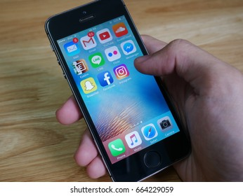 Bangkok, Thailand - June 21, 2017 : Apple iPhone5s held in one hand showing its screen with Snapchat, Facebook, Instagram and other applications.
