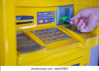 "Bangkok, Thailand - June 22, 2017: Man's hand inserting a credit card in ATM with ""Now safer This ATM is chip capable for cash withdrawal"" sticker sign attached to the machine, ATM security concept"