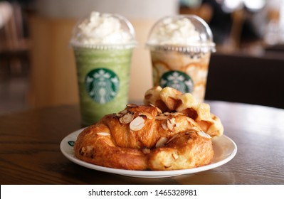 BANGKOK , THAILAND - JUNE 22 2019: new fresh almond criossant with greentea and coffee frappucino background at Starbucks