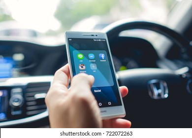 BANGKOK, THAILAND - June 24, 2017: Man in the car using Popular social media apps on Huawei smartphone, leisure & technology & internet addiction concept