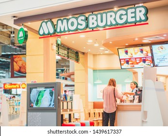 BANGKOK, THAILAND - June 25 , 2019: A customer buying foods and making checkout with cash desk worker at Mos Burger, a fast-food restaurant chain that originated in Japan.