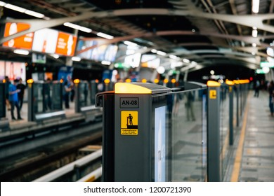 Bangkok, Thailand - June 25,2018: Platform screen doors. Do not lean against doors sign. People stand behind the yellow line waiting BTS Skytrain. Transportation in Bangkok City.