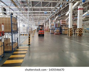 Bangkok, Thailand - June 26, 2019: Warehouses worker with forklift transports goods in a full warehouse