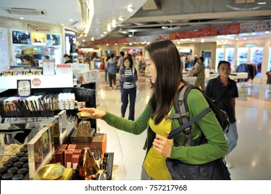 Bangkok, Thailand - June 28, 2012: An air traveler browses a duty free shop at Suvarnabhumi Airport.