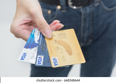 BANGKOK, THAILAND JUNE - 29 2017: Close up of the many expired credit card or visa card on female hand or young woman showing her many credit card