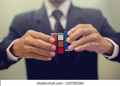 BANGKOK, THAILAND - JUNE 5, 2018: Businessman holding Rubik's cube - business solving problem and brain training concept.