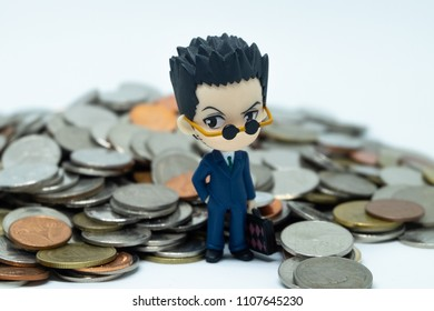 BANGKOK, THAILAND - JUNE 5, 2018: Figure Salaryman Stands in front of Mountain of Coins. Working for Money Concept.