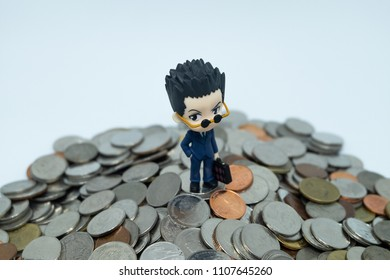 BANGKOK, THAILAND - JUNE 5, 2018: Figure Salaryman Stands on Mountain of Coins. Working for Money Concept.