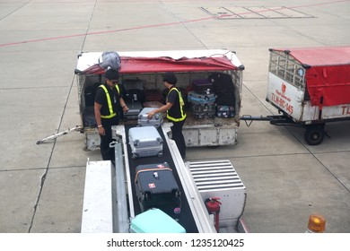 Bangkok Thailand - June 6, 2018: Baggage handler loading luggage on the ramp out of a plane, Worker arranging luggage on trailer connected to airplane, Don Muang international airport