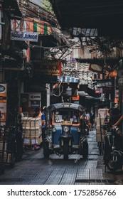 Bangkok, Thailand - June 6, 2020: Tuk Tuk taxi tricycle on small street  in the alley at Yaowarat area, Bangkok. Soft focus.