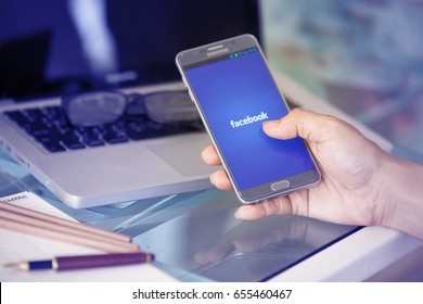 Bangkok, Thailand - June 6,2017: Facebook app on the Apple iPhone display and desktop version of Facebook on the Apple Macbook Pro Retina. Multi devices multitasking concept. All gadgets in full focus