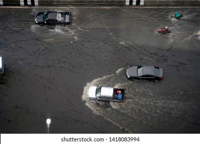 Bangkok Thailand - June 7, 2019. Top view of heavy flooding street in Bangkok city of Thailand after heavy raining. Cars and motorcycle running through the flood street.