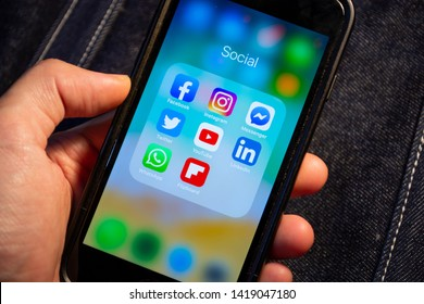 Bangkok, Thailand - June 7, 2019 : Apple iPhone 7 held in one hand showing its screen with Facebook, Instagram, Messenger, Twitter, YouTube, LinkedIn, WhatsApp and Flipboard.