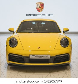 Bangkok, Thailand - June 8, 2019: the front view of a yellow Porsche 911 Carrera 4S with a screen behind showing the logo of Porsche in a car showroom at IconSiam shopping mall.