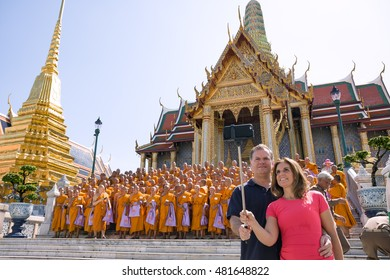 Bangkok, Thailand - June 9, 2015: Couple of tourists take a selfie while group of monks taking group photo in front of Prasat Phra Thep Bidon in Grand Palace--is the top tourist attractions in Bangkok
