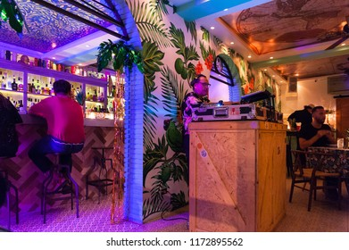 Bangkok, Thailand - June, 9, 2018 : Dj mixing at pub & restaurant party with crowd of people in background. Summer nightlife view of disco club, Bangkok