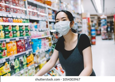 Bangkok, Thailand - Mar 22, 2018: Asian woman running errands in supermarket with mask on her face