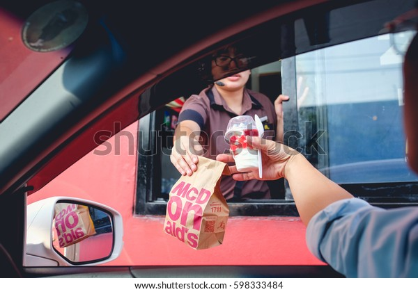 Bangkok, Thailand - Mar 4, 2017: Unidentified customer receiving hamburger and ice cream after order and buy it from McDonald's drive thru service, McDonald's is an American fast food restaurant chain