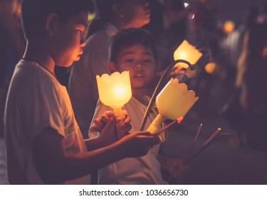 BANGKOK THAILAND - March 1, 2018: children  put the candle for respect to Buddha after walk with lighted candles in hand around a temple in   Makha Bucha Day on March 1, 2018 in Bangkok,Thailand.
